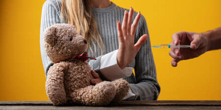 Woman making a stop gesture with her hand towards a vaccine while protecting her teddy bear in a conceptual image. Standard-Bild
