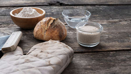 Still life with freshly baked homemade sourdough bread next to kitchen mitten, starter yeast, flour and water. Standard-Bild