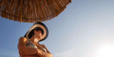 Low angle view of a young woman in a bikini and sunhat standing under sun umbrella on a beautiful clear summer day. Standard-Bild