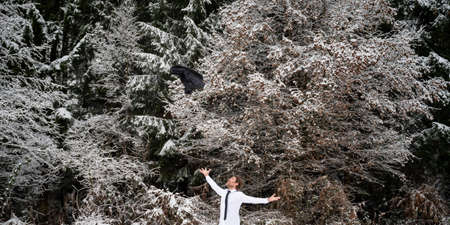 Cheerful young businessman standing in snowy winter nature celebrating success by throwing his suit jacket high up in the air. Standard-Bild