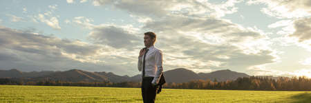 Confident young businessman standing with his jacket over the shoulder in a beautiful green meadow, looking into the distance with trust.
