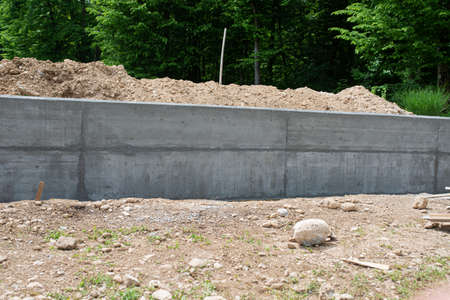 Concrete wall as a border between two pieces of land outside in a construction site. Standard-Bild