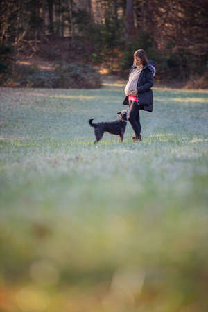 Young pregnant woman with big belly standing in beautiful autumn meadow with her pet dog.