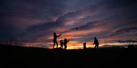 Silhouette of a young family of five playing with a ball outside under dramatic beautiful sky at sunset.