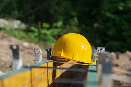 Yellow hardhat resting on a framework of wooden panels outside in a construction site.