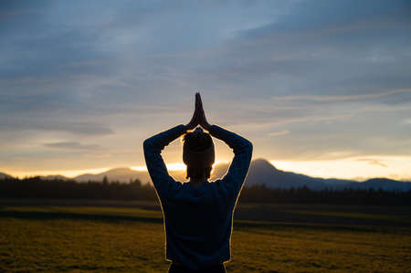 View from behind of a young woman meditating with her hands joined above her head outside in beautiful nature at sunset glowing in dramatic sky.