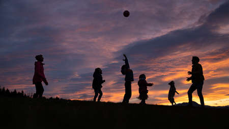 Silhouette of a family playing and having fun outside under beautiful cloudy sky at sunset.