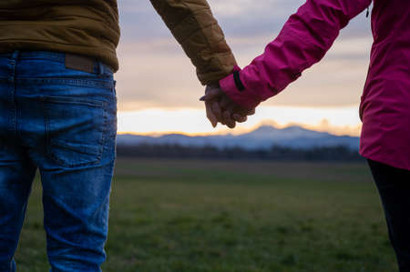 Closeup view of a couple holding hands standing outside in a beautiful meadow with mountains in the distance.