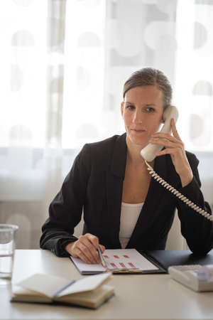 Young businesswoman sitting at her office desk talking on a phone while reviewing document and report with graphs and charts. Standard-Bild