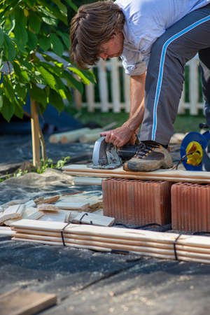 Young man working on a diy project outside in backyard sawing wooden planks for a fence. Standard-Bild