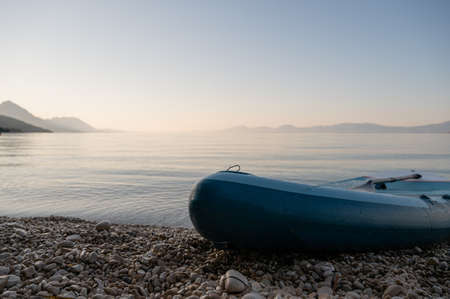 Low angle view of a sup board on shore of beautiful pebble beach and calm morning sea.