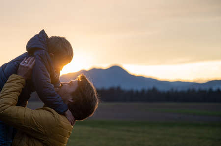 Happy young father lifting his son while playing outside in a beautiful meadow at sunset. Standard-Bild