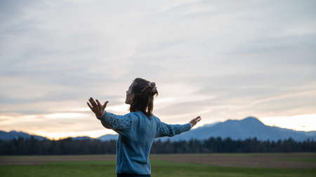 Young woman in casual clothing standing under a beautiful cloudy evening sky with her arms spread widely, enjoying life and prosperity.