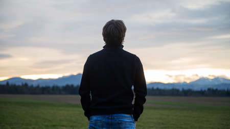 View from behind of a young man standing under a beautiful evening sky in a green meadow relaxing, enjoying and meditating.