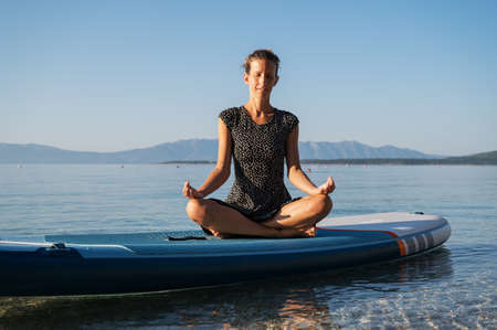 Young woman meditating in lotus position sitting on a sup board floating on calm morning sea water.