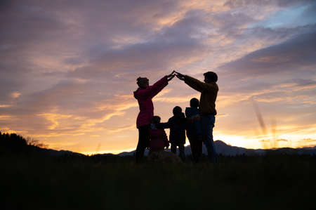 Silhouette of a family outside under a beautiful evening sky with parents making a house with their arms over their three kids and a dog.