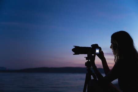 Young female photographer setting up her camera on a tripod at dusk by the sea. Standard-Bild