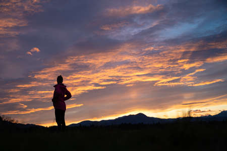 Low angle view of a young woman standing on and ascent in beautiful nature under a glowing evening sky.