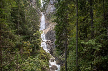 Beautiful waterfall falling down the rocks in green summer forest.
