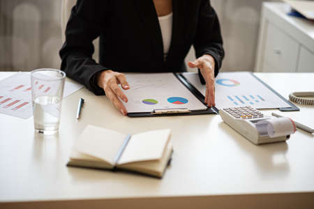 Businesswoman sitting at her desk working on financial report with graphs and charts. Archivio Fotografico