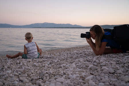 Young female photographer taking a low angle view photo of a toddler boy playing on a pebble beach in the evening.
