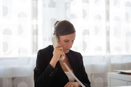Young businesswoman, secretary, sitting ate her office desk talking on a white landline telephone.