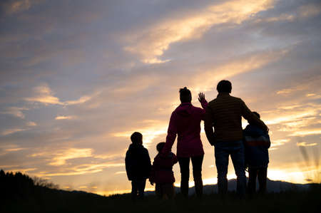Silhouette of a family of five standing under a beautiful evening sky looking into the distance towards the glowing light of a setting sun. Archivio Fotografico