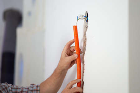 Closeup view of a workers hands positioning orange corrugated tube into a hole in a wall as a part of electrical installation. Archivio Fotografico