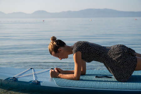 Young woman holding a plank position exercising on a sup board floating on calm morning sea. Archivio Fotografico
