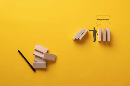 Silhouette of a man stopping collapsing dominos with a No problem speech bubble  in a conceptual image. Over yellow background. Archivio Fotografico