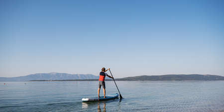 View from behind of a young man paddling on a sup board floating on calm morning sea water.
