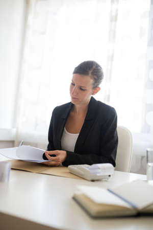 Young businesswoman sitting at her office desk checking and reading report and paperwork.