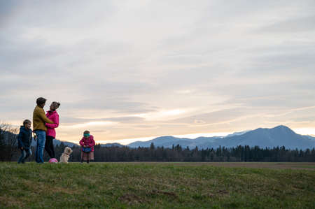 Beautiful family moment with parents hugging and children playing with their pet dog outside under the evening sky in beautiful meadow.
