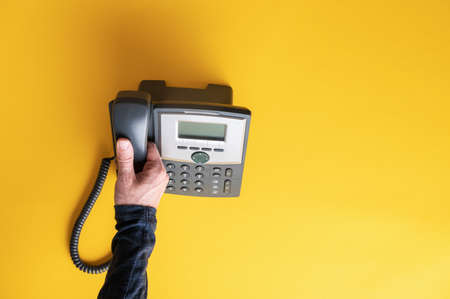 Top view of male hand picking up telephone receiver of a black landline phone. Over yellow background. Archivio Fotografico