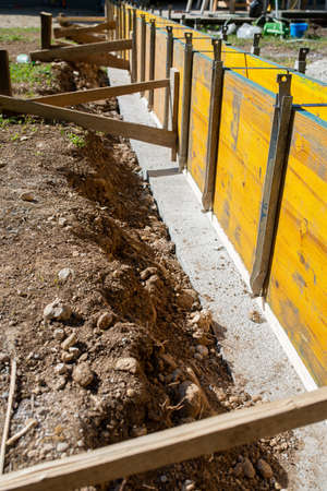 Construction site outside in backyard of a framework of wooden panels ready for cement to be poured in.