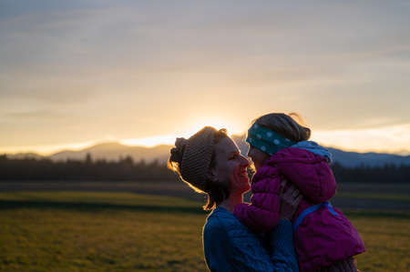 Cheerful smiling young mother lifting her toddler daughter while outside in a beautiful meadow at sunset.