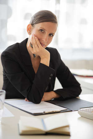 Young businesswoman sitting at her office desk with reports and paperwork in front of her leaning on her arm looking at the camera. Archivio Fotografico