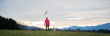 Wide view image of young woman throwing a toy for his pet dog outside in beautiful meadow.