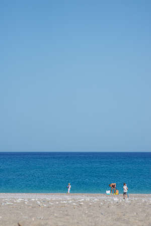 Distant view of a family setting their towel on a beautiful pebble beach by the blue sea.