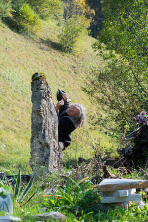 Senior artist carving in large stone with enthusiasm outside in beautiful green nature. Archivio Fotografico