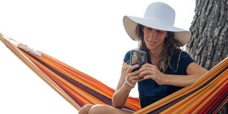 Relaxed young woman with sunhat sitting in hammock browsing on her mobile phone.