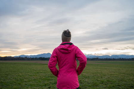 View from behind of a woman in bright pink jacket standing in beautiful meadow under an evening sky looking into the distance.