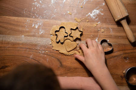 Top view of a child pressing various shaped cookie cutters in a vegan dough rolled on wooden table.