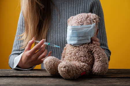 Closeup view of a woman vaccinating a teddy bear in a conceptual image of pediatric healthcare.