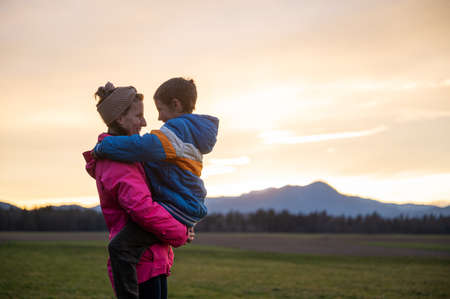 Happy smiling young mother holding his son in her arms looking at him lovingly as they stand outside in beautiful meadow under an evening sky.