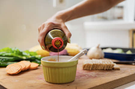 Closeup view of a woman pouring soya sauce into a cup to prepare a dip on wooden cutting board full of vegetables and vegan protein.