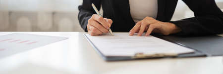 Wide view closeup image of a businesswoman signing a document or application form in a folder.