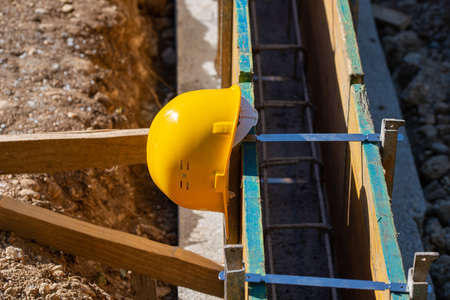 Yellow protective hardhat resting on a framework of wooden panels in a construction site.