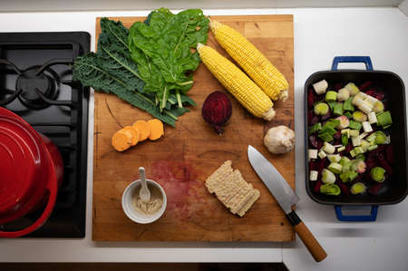 Top view of colorful fresh vegetables such as corn, beets, kale and vegan protein on a wooden cutting board.