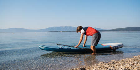 Young man about to go on a sup board to paddle on a calm morning sea water.